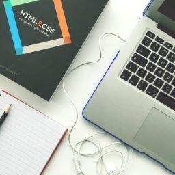 Laptop, notatnik i książka do nauki HTML i CSS